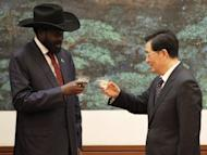 """Chinese President Hu Jintao (right) and South Sudan President Salva Kiir toast after a signing ceremony at the Great Hall of the People in Beijing on April 24, 2012. Kiir will cut short his visit to China due to """"domestic issues"""", a Chinese official said Wednesday, as violence between the world's newest nation and Sudan intensified"""