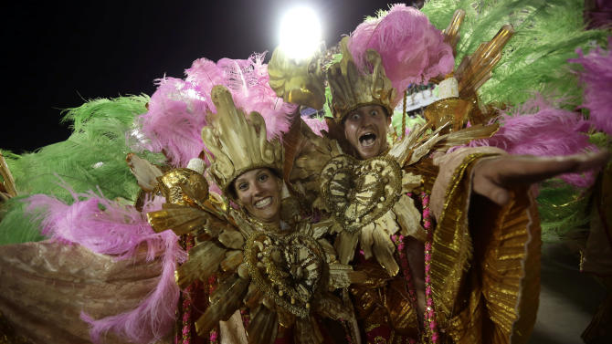 "U.S. citizen Paul Leaury, right, and an unidentified fellow foreign member of the Mangueira samba school, dance during a carnival parade at the Sambadrome in Rio de Janeiro, Brazil, Tuesday, Feb. 12, 2013. While non-Brazilians have long shelled out hundreds of dollars for the right to dress up in over-the-top costumes and boogie in Rio's samba school parades, which wrapped up Monday in an all-night extravaganza, few in the so-called ""alas dos gringos,"" or ""foreigners' wings,"" know how to dance the samba well, bopping along goofily in the parades and waving at the crowds of spectators. (AP Photo/Silvia Izquierdo)"