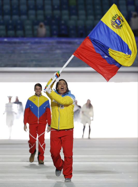 Antonio Pardo of Venezuela carries the national flag as he leads the team during the opening ceremony of the 2014 Winter Olympics in Sochi, Russia, Friday, Feb. 7, 2014. (AP Photo/Mark Humphrey)