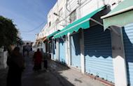Libyans walk past closed shops in the capital Tripoli at the start of a three-day strike in Tripoli on November 17, 2013