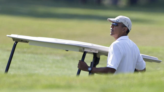 President Barack Obama holds onto a golf cart as he looks toward the green while golfing at Farm Neck Golf Club in Oak Bluffs, Mass., on the island of Martha's Vineyard, Saturday, Aug. 17, 2013. (AP Photo/Steven Senne)