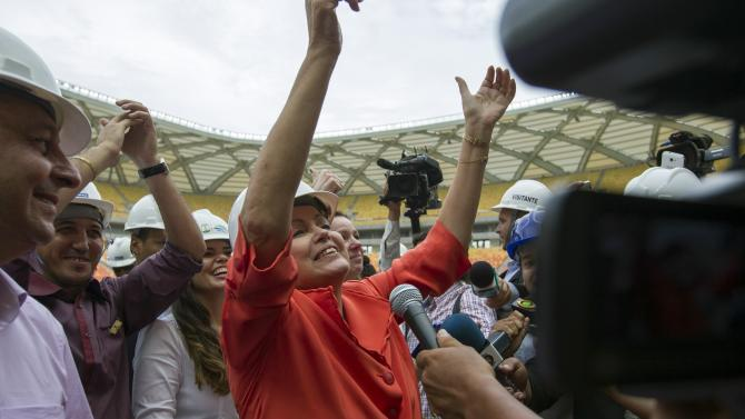 Brazil's President Dilma Rousseff gestures to workers as she visits the Arena Amazonia stadium in Manaus