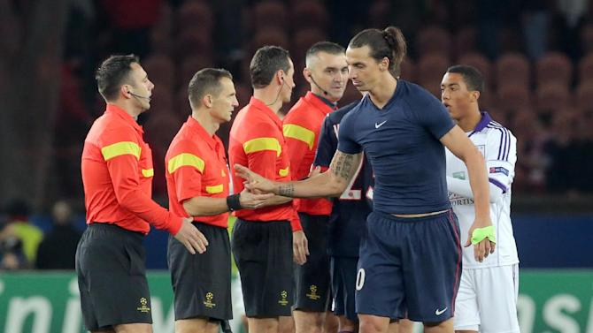 PSG's Zlatan Ibrahimovic shakes hands with unidentified referees at the end of his Champions League group C soccer match against Anderlecht in Paris, France, Tuesday, Nov. 5, 2013. The match ended in a 1-1 draw
