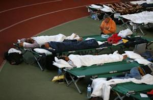 A man prays as other migrants rest on beds at an improvised…