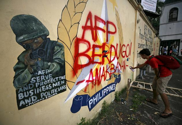 A youth activist vandalises the seal of the Armed Forces of the Philippines outside their headquarters in Camp Aguinaldo, Quezon City, metro Manila