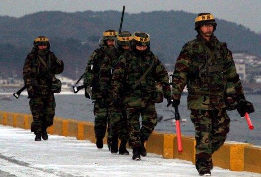 South Korean marines patrol along the wharf on Yeonpyeong island near the maritime border between the two Koreas on December 17, 2010. The country's marines staged a live-fire exercise Wednesday near the disputed Yellow Sea border with North Korea amid high tensions over a display of front-line Christmas lights.