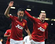 Manchester United's Ryan Giggs (L) celebrates with Wayne Rooney after scoring a penalty during their 4-1 FA Cup football win over Fulham at Old Trafford on January 26, 2013