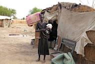 Nyrop Nyol stands outside her home in Wunchuei, near the contested region of Abyei in March. South Sudan has withdrawn hundreds of police from the territory of Abyei that it disputes with Sudan ahead of a UN Security Council ultimatum, a UN spokesman said