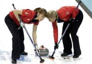 Britain's Claire Hamilton (L) and vice Anna Sloan sweep the ice during their women's curling semifinal game against Canada at the 2014 Sochi Winter Olympics in the Ice Cube Curling Center in Sochi February 19, 2014. REUTERS/Ints Kalnins