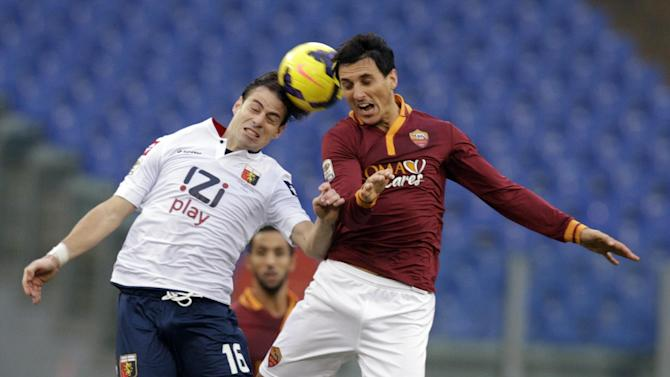 Genoa forward Emanuele Calai, left, and AS Roma defender Nicolas Burdisso, of Argentina,  jump for the ball during a Serie A soccer match between AS Roma and Genoa, at Rome's Olympic Stadium, Sunday, Jan. 12, 2014