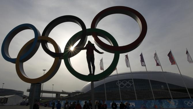 A woman stands in a set of Olympics rings as she has her picture taken at the Olympic Park a day after the closing ceremony for the 2014 Sochi Winter Olympics