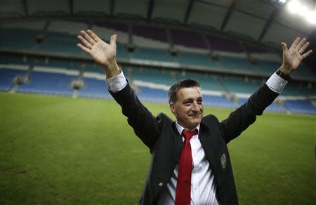 Gibraltar's coach Allen Bula greets supporters after his team's international friendly soccer match against Slovakia at Algarve stadium near Faro