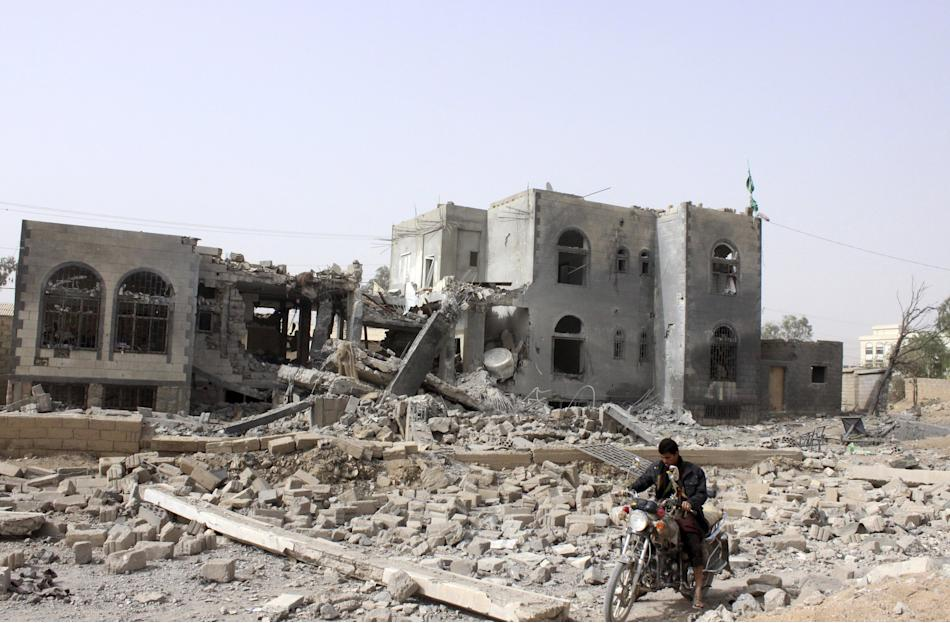 A man rides a motorcycle past a headquarters of the Houthi group, which was destroyed after an air strike by a Saudi-led coalition, in Yemen's northwestern city of Saada