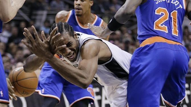 San Antonio Spurs' Kawhi Leonard, left, loses control of the ball as he is defended by New York Knicks' Iman Shumpert (21) during the first half of an NBA basketball game, Thursday, Jan. 2, 2014, in San Antonio