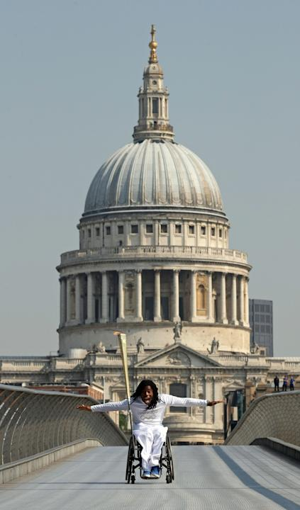 In this photo provided by LOCOG, torchbearer Ade Adepitan carries the Olympic Flame on Millennium Bridge during Day 69 of the London 2012 Olympic Torch Relay, Thursday, July 26, 2012, in London. (AP P