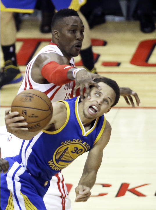 Houston Rockets' Dwight Howard, left, pressures Golden State Warriors' Stephen Curry in the first half of Game 3 of the Western Conference finals NBA basketball playoff game Saturday, May 23,