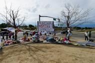 People continue to visit the roadside memorial set up for victims of the Colorado theater shooting massacre across the street from Century 16 movie theater on July 29 in Aurora, Colorado