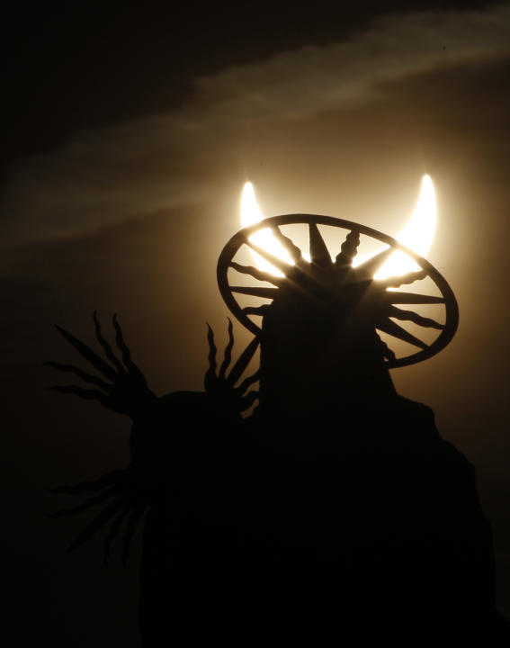 A statue is silhouetted against a partial solar eclipse in Prague, Czech Republic, Tuesday, Jan. 4, 2011. (AP Photo/Petr David Josek)