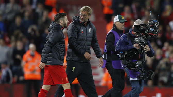 Liverpool manager Juergen Klopp speaks with Adam Lallana after the game