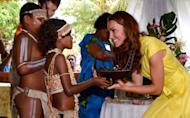 Catherine, the Duchess of Cambridge (R) is presented with a small canoe by two local children during a visit to the Commonwealth Youth Programme in Honiara on September 17, 2012. William, second in line to the British throne, said he was thrilled by their welcome to the lush Pacific island, putting on a brave face despite the photo row, which has cast a shadow over their trip