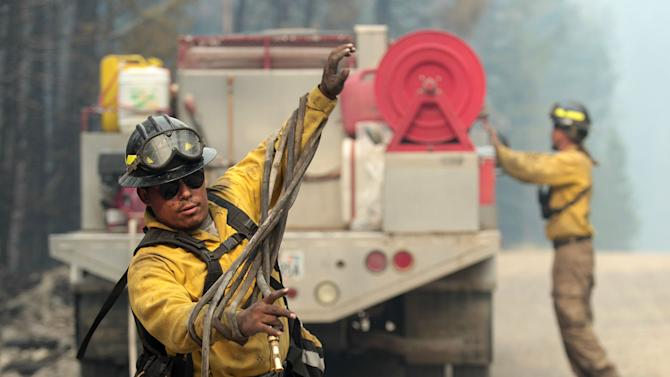 In this Monday, Aug. 19, 2013 photo, firefighters with the private contract company Great Basin Fire, mop up part of the 104,457-acre Beaver Creek Fire in the Baker Creek, north of Ketchum, Idaho. (AP Photo/Times-News, Ashley Smith)