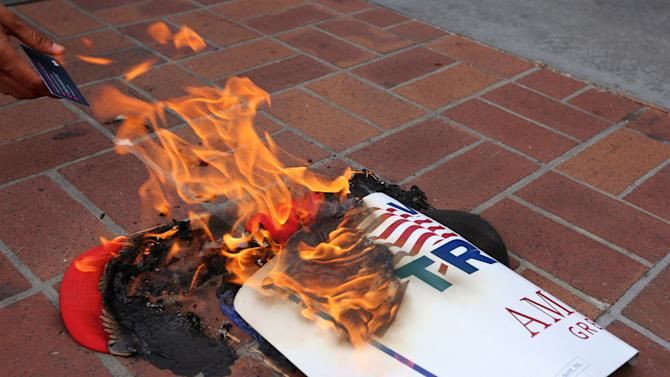 Anti-Trump demonstrators burn Trump's campaign items outside a campaign event for Republican U.S. presidential candidate Donald Trump in San Diego