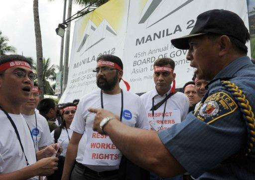 A Philippine policeman (R) argues with foreign delegates to the Asian Development Bank board of governors annual meeting