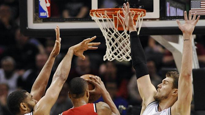Portland Trailblazers guard Damian Lillard, center, shoots between San Antonio Spurs forwards Tim Duncan, left, and Tiago Splitter, of Brazil, during the first half of an NBA basketball game on Wednesday, March 12, 2014, in San Antonio