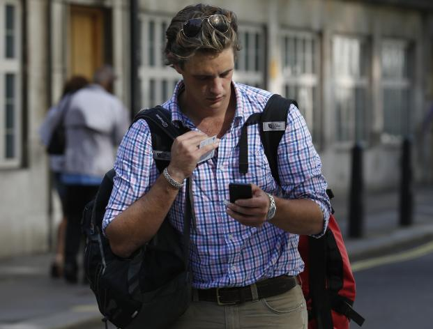 A man checks his mobile phone in central London August 30, 2013. Verizon is close to buying the 45 percent stake in the joint venture Verizon Wireless from Vodafone, according to sources. REUTERS/Olivia Harris (BRITAIN - Tags: BUSINESS TELECOMS)