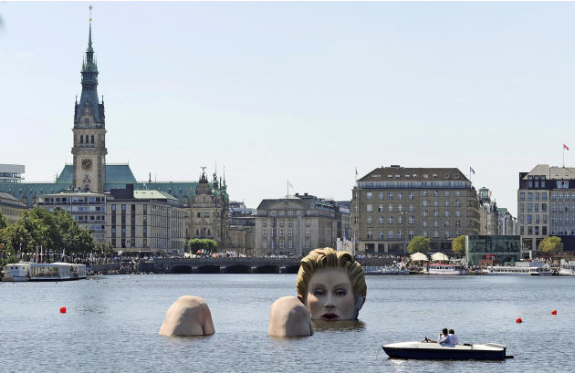 A boat passes a sculpture of a giant mermaid designed by German artist Oliver Voss on the river Alster in Hamburg, northern Germany, Tuesday, Aug. 2, 2011. The sculpture made of styrofoam and steel wi