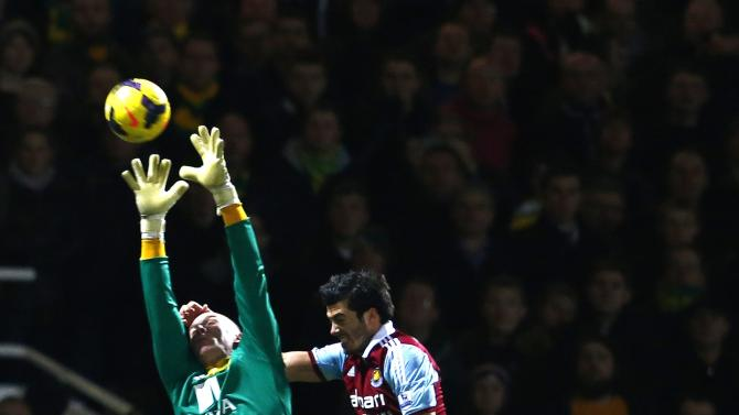 West Ham United's Tomkins challenges Norwich City goalkeeper Ruddy during their English Premier League soccer match at the Boleyn Ground in London