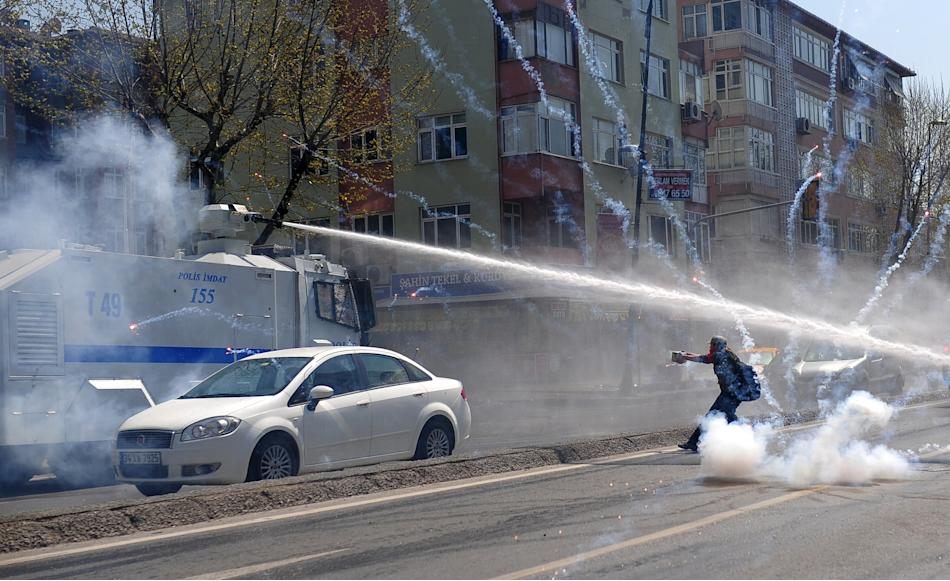 Police use tear gas and water cannons against leftist protesters, as one of them shoots firecrackers at an armoured police vehicle, during clashes after the office of Istanbul's Governor banned th