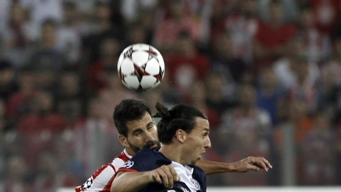 Olympiakos' Siovas fights for the ball against Paris St Germain Ibrahimovic during their Group C Champions League soccer match in Piraeus