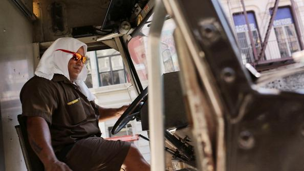 A UPS driver keeps a towel on his head while driving along Broadway during warm weather on July 6, 2012 in New york City. Forecasts for tomorrow are predicting temperatures near 100 degrees Fahrenheit (38 Celsius) and may feel as hot as 106 because of humidity, according to the National weather Service. Much of the midwest of the United States has been experiencing a severe heat wave which has devastated crops and kept people indoors. (Photo by Spencer Platt/Getty Images)