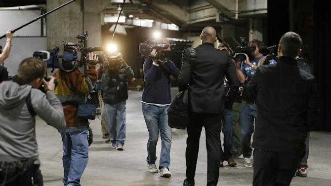 Members of the media and television crews follow Los Angeles Lakers' Kobe Bryant as he arrives at Staples Center before the NBA basketball game against the Toronto Raptors  in Los Angeles, Sunday, Dec. 8, 2013. Bryant is expected to make  his long-awaited return from a torn left Achilles tendon injury from April 12th