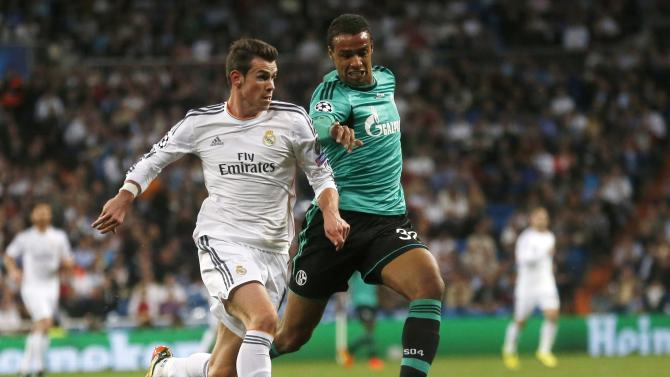 Real Madrid's Gareth Bale challenges Schalke 04's Joel Matip during their Champions League last 16 second leg soccer match at Santiago Bernabeu stadium in Madrid