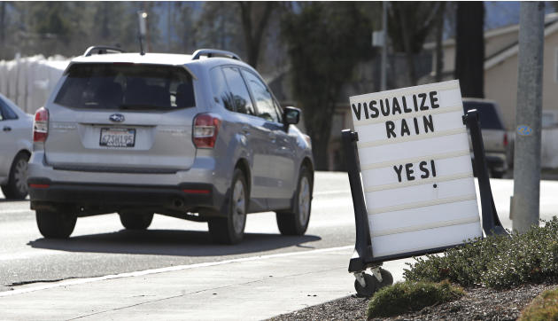 FILE - In this Feb. 4, 2014 file photo, cars drive past a sign outside of a market reminding residents about the short water supply in Willits, Calif. State public health officials have reduced the nu