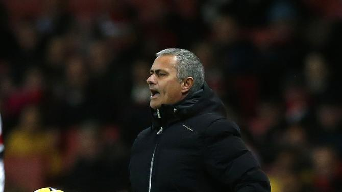 Chelsea's manager Mourinho shouts to his players as he holds a ball during their English Premier League soccer match against Arsenal at The Emirates in London