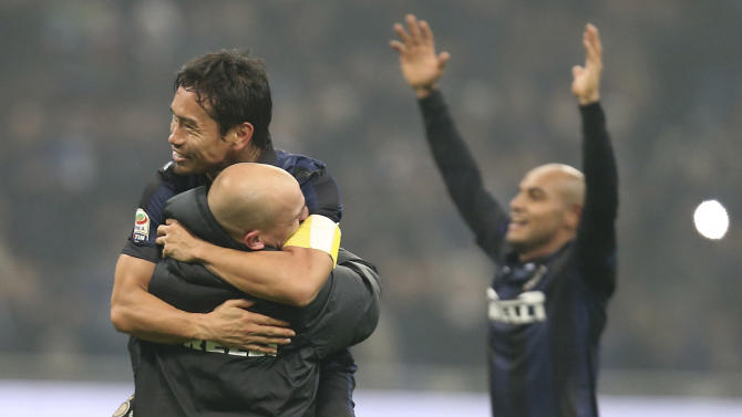 Inter Milan defender Yuto Nagatomo, top left, of Japan, hugs his teammates Argentine midfielder Esteban Cambiasso at the end of the Serie A soccer match between Inter Milan and AC Milan at the San Siro stadium in Milan, Italy, Sunday, Dec. 22, 2013. A late goal from Rodrigo Palacio gave Inter Milan a 1-0 win over city rival AC Milan in an entertaining derby match in Serie A on Sunday. Palacio struck four minutes from time to send three quarters of San Siro into a frenzy