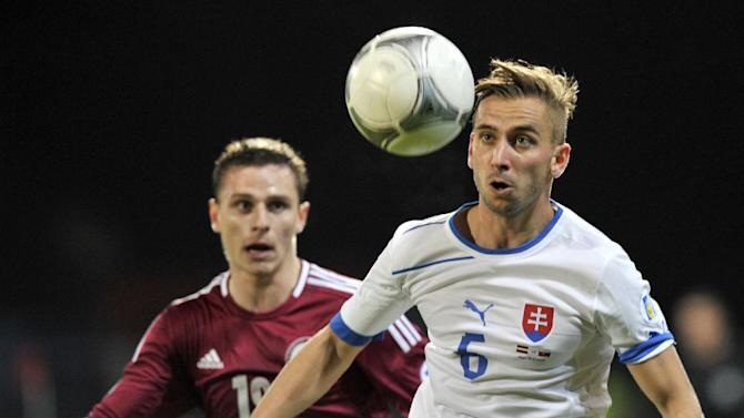 Latvia's Andrejs Kovalovs, left, vies for the ball with Slovakia's Dusan Svento during a World Cup 2014 Group G qualification match in Riga, Latvia, on Tuesday Oct. 15, 2013