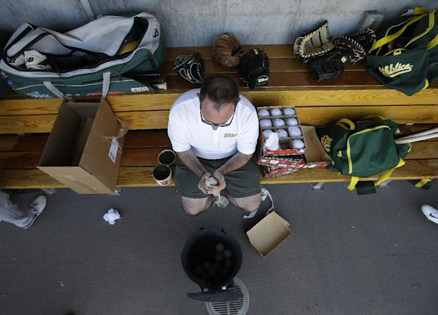 """FILE - In this March 6, 2015, file photo, Oakland Athletics' Mike Thalblum rubs new baseballs with """"Baseball Rubbing Mud"""" during a spring training game between the Arizona Diamondbacks and Oakland Athletics in Scottsdale, Ariz. Even before the Tom Brady scandal broke, Major League Baseball was pumping up security for its game balls this season. An MLB representative now watches the baseballs while a clubhouse assistant carries them from the umpires' room to the field. (AP Photo/Darron Cummings, File)"""