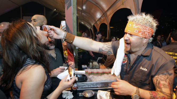 Guy Fieri, right, feeds Rachael Ray, left, at the South Beach Wine and Food Festival's Burger Bash, Friday, Feb. 22, 2013, in Miami Beach, Fla. (AP Photo/Luis M. Alvarez)