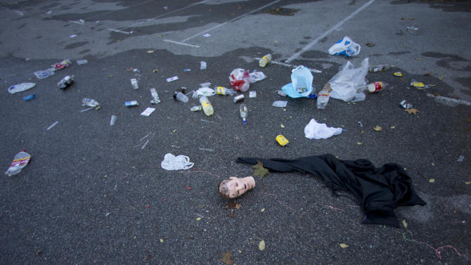 A mannequin's head, bottles and and other debris lie in the Madrid Arena venue car park Madrid, Thursday Nov. 1, 2012. Three women have been killed and two injured in a stampede during a large Halloween Night party at a Madrid indoor venue. Emergency services spokesman Fernando Prado said the women, aged between 18-25 years old, suffered trauma injuries and heart failure compatible with having been crushed during a stampede after a flare was reportedly set off within Madrid Arena in the west of the city, where thousands of people were partying early Thursday. Halloween has recently become a popular festivity in Spain coinciding with the traditional feast of All Saints. (AP Photo/Paul White)