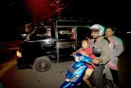 Residents drive to higher ground after a 5.9-magnitude earthquake struck 112 km southeast of the Indonesian capital of Banda Aceh on January 22, 2013. An eight-year-old girl was killed and seven others were injured, officials said
