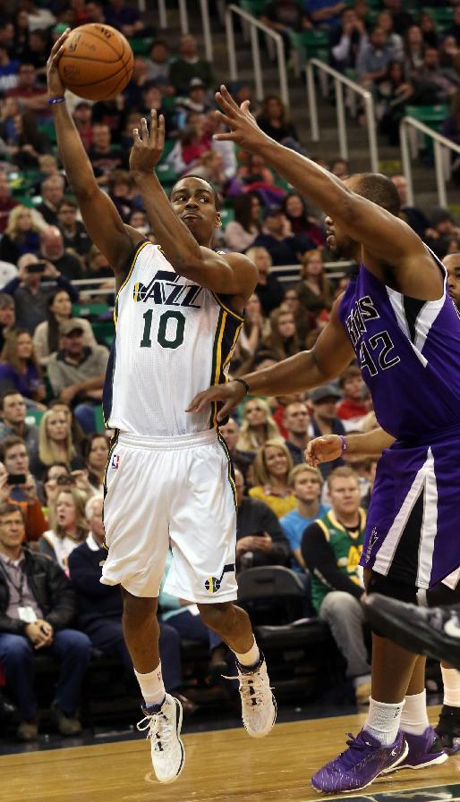 Utah Jazz's Alec Burks (10) passes the ball as Sacramento Kings' Chuck Hayes (42) defends in the second half of an NBA basketball game on Saturday, Dec. 7, 2013, in Salt Lake City. The Kings went on to win 112-102 in overtime