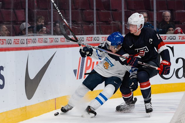 Jack Eichel #9 of the U.S. checks Mika Ilvonen #4 of Team Finland into the boards during the 2015 IIHF World Junior Hockey Championship game at the Bell Centre. (Photo by Minas Panagiotakis/Getty Images)