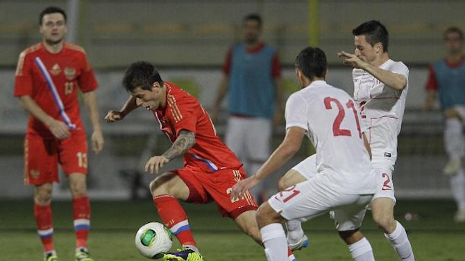 Russia's Fedor Smolov, second left, runs with the ball among Serbian players during a friendly match Dubai, United Arab Emirates, Friday Nov. 15, 2013