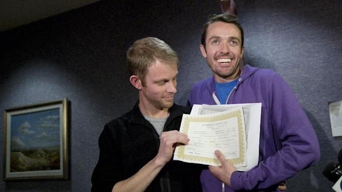 Seth Anderson, left, and Michael Ferguson, right, hold up their marriage certificate and license outside of the Salt Lake County Clerk's Office in Salt Lake City Friday, Dec. 20, 2013. A federal judge struck down Utah's same-sex marriage ban Friday in a decision that marks a drastic shift toward gay marriage in a conservative state where the Mormon church has long been against it. (AP Photo/Kim Raff)
