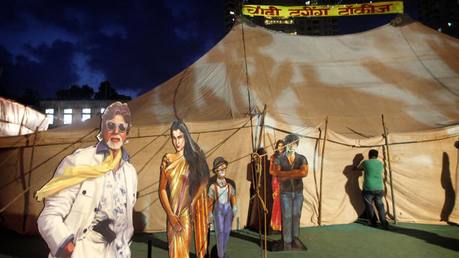 """In this April 20, 2013 photo, cut outs of Indian Bollywood stars are displayed on the premises of the Anup Touring Talkies tent cinema in Mumbai, India. Friday, May 3 marks exactly a hundred years after India's first feature film """"Raja Harischandra,"""" a silent movie, was screened in 1913. India produced almost 1,500 movies last year and the industry is expected to grow from $ 2 billion to $ 3.6 billion in the next five years, according to consultancy KPMG. (AP Photo/Rajanish Kakade)"""