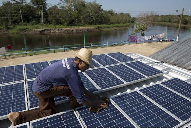 Francisco da Silva Vale cleans solar panels which power ice machines at Vila Nova do Amana community in the Sustainable Development Reserve, in Amazonas state
